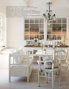 this dining room is cottage chic with an elegant chandelier and bench for seating