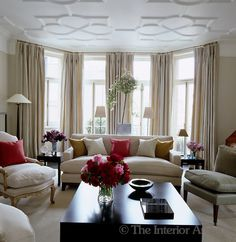 Carlos Mota ~ The elegant living room has a floor-to-ceiling bay window and a moulded ceiling