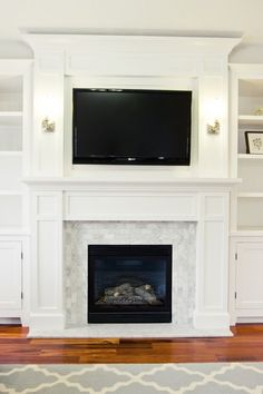 Fireplace millwork 4: beautiful example, with or without the crown molding capping the top panel. Either would look good in your space. Again, notice the squared, angular trimwork detail surrounding the fireplace; a nice compliment to your ceiling.