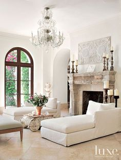 This grand living room is so classy! Neutral coloring, a stone fireplace mantel w/ vintage candlesticks, & an intricate white chandelier exude elegance & sophistication.