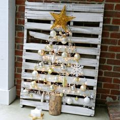 I saved this pallet headed for the trash, and transformed it into a Christmas tree using ornaments from the thrift store and a split log.