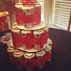 Budweiser beer cake, I wasnt going to use card board on to make the next level of the cake but realized you have to. All together is budweiser cans, red streamer, some cardboard I cut and a bow.