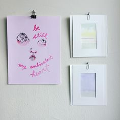 """New additions to the office. Left by @ambivalentlyyours right by Lu Peirera. [Picture of three pieces of art hung on a white wall. Letter sized print on left all in pink has a face with the words """"be still my ambivalent heart"""" two small pastel water colours matted in white water colour paper on right]"""