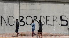 """- Refugiados passam em frente a um muro com os dizeres """" Sem Fronteiras"""", na Cidade Portuária de Pireu, na Grécia. Foto: Thanassis Stavrakis / AP"""