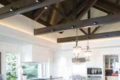 Contemporary kitchen in white, with vaulted ceilings.