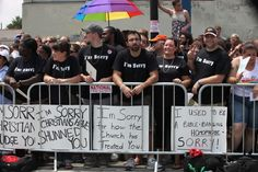"""A group of Christians at a pride parade with signs such as """"I used to be a bible-banging homophobe. Sorry!"""""""