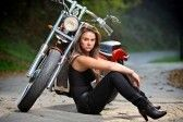 Biker girl sitting next to a bike stock photography
