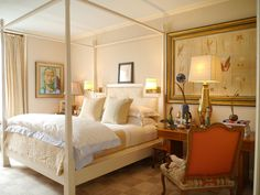Nancy Boszhardt--her bedroom in NYC:  A custom canopy bed made up in linens from Casa Del Bianco.  The walls are upholstered in a fabric from Norbar. The large framed botanical collection above the writing table is from Marché aux Puces.