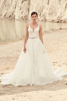 Mikaella Bridal wedding dress | Style 2120 | Mikaella Lace and Organza #WeddingDress. Lace gown with multiple crossover straps at back. Fit and flare lace skirt. Full circle detachable overskirt in Organza with center front opening. Detachable overskirt with lace waistband and removable beaded appliqué.