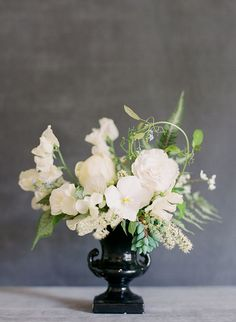 This reclaimed footed black ceramic compote contains peonies, begonias, ranunculi, mahonia berries, painted ferns, chokecherry blossoms, bignonia vines, and forget-me-nots. | Floral design by Nature Composed | Photos by Jodi Miller Photography