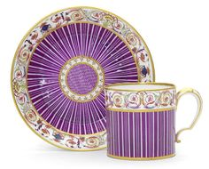 A Sèvres hard-paste cup and saucer, circa 1785. Gobelet 'litron' of the second size, painted by Louis-Antoine Le Grand (fils) with a puce striped pattern within a thin gilt band, a colourful scrolling foliate and floral border interspersed with urns, butterflies and fan-shapes to the gilt-edged rims, a puce diamond-pattern-ground surrounded by a gilt-edged band of foliate C-scrolls to the centre of the saucer, crowned interlaced LL monogram with painter's mark in gilding, incised marks to…