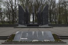 Latvian Soviet Socialist Republic. Victory Day Memorial located at Dubrovin park in Daugavpils. A memorial was erected on the mass grave. In its center there are 7 wedge-shaped granite monuments on which metal plates with the names of buried warriors are attached. In front of the memorial, a commemorative slab with the year of liberation of the city is installed, behind there is a stone ridge with an inscription. The author of the memorial opened in 1984 was the sculptor Vladimir Ivanov. Monumentos, Granito, Guerreiros, Passeio, Nomes, Autor, Parque