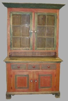 "PENNSYLVANIA TWO-PIECE STEPBACK CUPBOARD. Attributed to Soap Hollow. Poplar carefully dry scraped down to the remaining original red and green paint. Black paint on the feet. Dovetailed bracket feet and case with a simple beveled molding around the base. Two raised panel doors on the base   Three dovetailed drawers at the waist with a scrubbed pie shelf  Two-door top with six panes of old glass in each.High, canted cornice.Good size. 52""w. 23 1/4""d. 85 1/2""h."