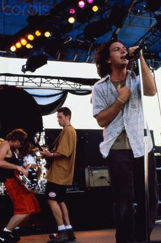 Eddie Vedder sings, while guitarist Stone Gossard and bass player Jeff Ament jam behind him, during a Pearl Jam concert.