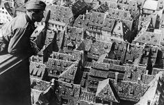 A German soldier looking at Strasbourg, France from the tower of the city's cathedral, 15 Jul 1940