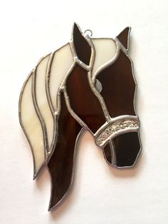 This handmade stained glass horse suncatcher is great for any country-themed home...and is a great gift for any horse lover!! This suncatcher is made with opaque/semi-translucent brown and light cream glass; the bridle is made of textured silver glass)  NOTE ABOUT CUSTOMIZATION: I can make this horse in any color(s) you wish. If you are interested in a customized horse, feel free to convo me and specify your choice of colors for the mane and for the face/ears/neck. Approximately 8.00H x…
