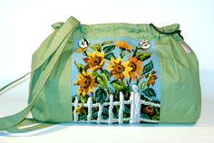 Die Tasche ist aus lindgrünem Jeans. Auf der Vorderseite ist ein großes Bild aufgenäht mit gelben Sonnenblumen.  Dieses Gobelin Bild ist in liebevo...