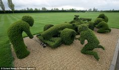 """The pit crew changes tires on a """"green"""" Formula 1 car located on the grounds of the Williams F1 headquarters near Didcot (Oxfordshire) England."""