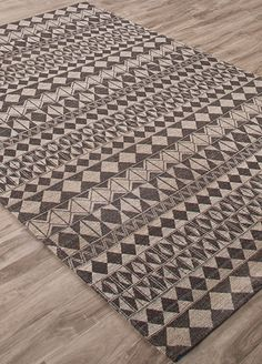 Tightly arranged, geometric patterns reminiscent of French Polynesian grass-cloth designs adorn this easy-to-care-for, flat-weave wool dhurrie in contrasting neutrals.