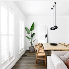 love the contrast of the white room with the black pendant lamps over the dining room