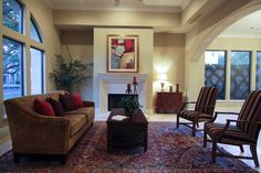 Formal living room offers a gas log fireplace with carved travertine marble surround, diagonally set travertine marble flooring and an arched opening to the dining room.