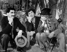 Scene from an unidentified Marx Brothers film, showing Groucho, Chico, and Harpo sitting down on buckets, resting their fists under their chins.