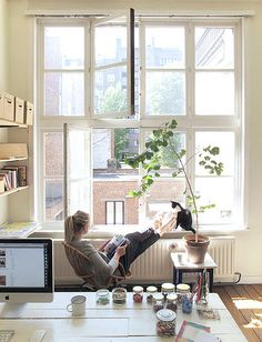 The home of Sophie Schellekens... relaxed shot in the window with feet up and a big plant nearby.