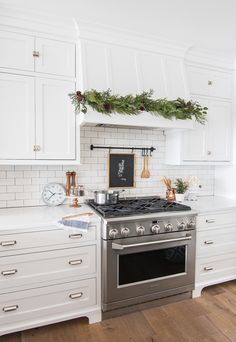 Christmas Kitchen decor - fresh greens and touches of Christmas in this white kitchen. Beautiful faux garland along range hood. #ChristmasDecor #ChristmasDecorations #HolidayHome #HolidayDecor