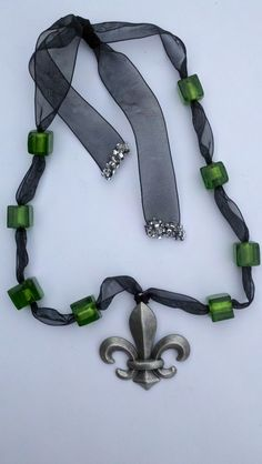 A Fleur de leis pendant wrapped in black ribbon that is threaded through emerald green glass. The tails are beaded to look like tiny diamonds as they drape down the back of your neck. Gorgeous! Item #502. $52.00
