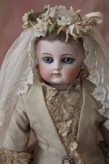 FG block letter bebe with early leather body, bisque forearms and original wedding gown, Paris late 1870s. www.museedelapoupeeparis.com #dollshopsunited