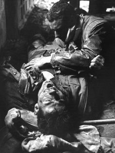 A seriously wounded Marine cries out and recites the Lord's Prayer as an injured comrade tries to comfort him at their outpost in a house in Hue's Citadel, Feb. 18, 1968.