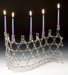 The Magen David, emblazoned on Israel's flag, is one of the most famous symbols of Judaism. The Menorah of Unity, designed as a series of interlacing six-pointed stars, is made out of heat-resistant glass, eliminating the need for metal inserts to hold the candles. It is available in five finish options. The 6 points represent 6 brave men - Mattathias and his five sons - who began the revolt at the heart of the Chanukah story. As they stood unified for religious freedom, so you, upon…
