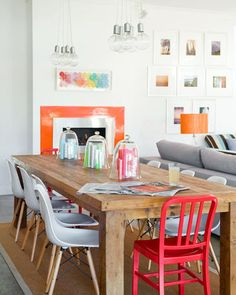 Once a flimsy verandah at the rear of the property, this space has been transformed into a vibrant dining zone. The gas fireplace, highlighted by a border in Burnt Orange from Solver Paints, marks the end of the old home and start of the extension. Pendant lights from 4M are suspended over the recycled teak table, custom-made by Chinta Design. Replica Eames 'Eiffel DSW' chairs and red Emeco 'US Navy' chairs from Matt Blatt lend an industrial edge.