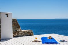 Set on a gentle slope just over the sea, this residence is unlike any other villa you'll find in Syros as its lofty vantage point offers unimpeded sea views. Luxury Villas In Greece, Square Meter, Outdoor Furniture, Outdoor Decor, Sun Lounger, Beach Mat, Outdoor Blanket, Sea, Chaise Longue