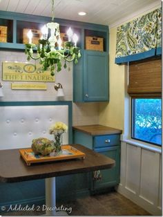I painted my kitchen walls about the color of the cabinets here. I love their valance/woven wood combo. Very nice! Plus, that eating nook is adorable!