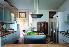 A cozinha contemporânea, projetada pelo arquiteto Jorge Siemsen, tem pitadas de rusticidade, como a parede de tijolinho, o piso e o armário ao fundo