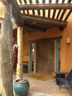 Southwestern style patio with rough wood columns, vitas, stucco and inspired by pueblo Indian style architecture