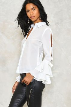 Love is an understatement. The Love to Splits Shirt features a pointed collar, button-up front, and tiered flute sleeves with slits and bow detailing.