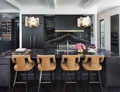 Black flat front cabinets compliment a large black oak kitchen island with black marble countertops and gold velvet upholstered island stools with a touch of vintage.