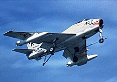 An FJ-3B Fury from VF-144 Squadron has its arrester hook down as it comes in to land.