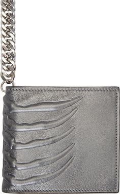 """Alexander McQueen Metallic leather bifold wallet in silver. Embossed ribcage at front, back, and fold. Silver-tone fixture strap with signature skull charm and lobster clasp closure. Contrasting interior in tangerine orange. Card slots, note compartments, coin pocket with press-stud closure, and embossed logo at wallet interior. Tonal stitching. Approx. 4.25"""" length x 4"""" height."""