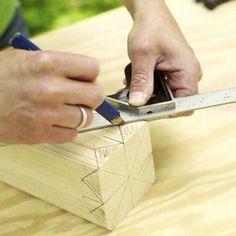 man marking wood to make king crown for yard game of kubb