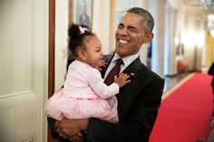 President Barack Obama holds the daughter of former staff member Darienne Page Rakestraw in the Cross Hall of the White House, April 3, 2015.