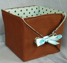 Building a Basket Using Vintage Fabrics and Grommets.  Doesn't give measurements but does give an image of the layout before folding it into a basket.