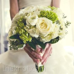 A lush bouquet of white ranunculus, roses and mini green hydrangeas blended together beautifully.