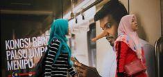 """i passanti vanno a Kuala Lumpur su un poster con la scritta """"Colui che condivide bugie diventa se stesso un bugiardo"""". Il parlamento malese ha approvato una nuova legge che vieta """"notizie false"""". I critici lo vedono come un tentativo di mettere a tacere voci sgradevoli."""