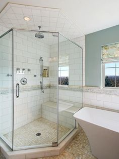 By tucking the curved freestanding tub into a corner by the window, designer Joan Suzio was able to capture space for the walk-in shower. A niche recessed in the wall is a tidy spot to place shampoos and soaps to keep them off the floor or bench.  Although a curbless shower with zero threshold was desired, the curb helps keep water off the bathroom floor.