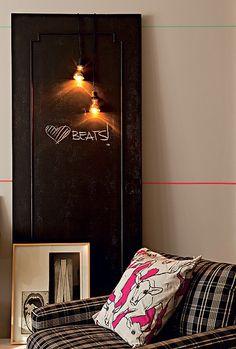 A porta velha virou suporte para duas lâmpadas, penduradas apenas pelos fios de eletricidade, e quadro de avisos