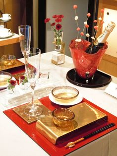 Japanese table setting with gold dinnerware set - gold serving plate, glass bowls, chopstick rest, champagne bucket and bud vase. Dinnerware by Glass Studio