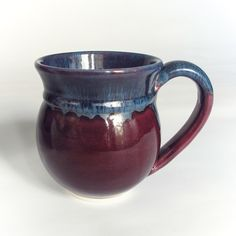 Wheel-thrown and elegantly shaped white earthenware eggplant / orchid purple mug with a handmade handle attached Glazed with an Aubergine Eggplant Purple lavender blush glaze and blue sea-froth on th See More. Purple Tea Cups, Purple Coffee Mugs, Coffee Cups, Pottery Mugs, Ceramic Pottery, Pottery Art, Pottery Ideas, Ceramic Cups, Ceramic Art